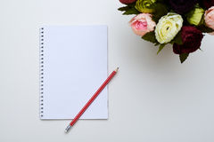 A white jotter and a red pencil next to peonies Stock Image