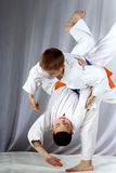 In white judogi two athletes are training throws Stock Photo
