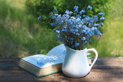 White jug with bouquet of forget-me-nots on  wooden table Royalty Free Stock Image