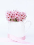 White jug with bouquet of pink flowers on a white background Stock Photo
