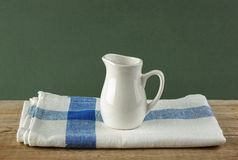 White jug and dishcloth on old wooden table Royalty Free Stock Image