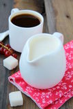 White jug with milk and coffee royalty free stock photography