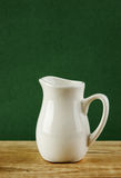 White jug on old wooden table Royalty Free Stock Photos