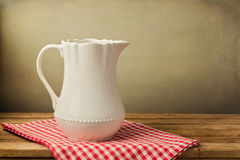 White jug on tablecloth. On wooden table over grunge background Stock Photo