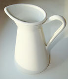 White jug. For watering flowers on a white windowsill Royalty Free Stock Photography