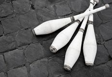 White juggling clubs on the street. White small toss juggling clubs resting on the street ground. Performing street art, sport and exercising Royalty Free Stock Photos
