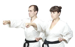 In white karategi the adult sportsmen are beating punch hand Royalty Free Stock Photography