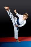 In white karategi boy doing kick yoko-geri right foot Stock Photography