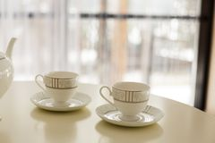 White kettle and two cups for tea on the table. royalty free stock photos