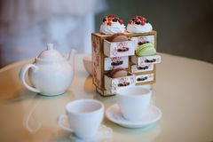 A white kettle, two mugs and cakes stock image