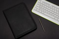 White keyboard on a black background with leather folder and pen. View from above. White keyboard on a black background with leather folder and pen. View from stock photo