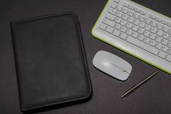 White keyboard on a black background with leather folder and pen. View from above. White keyboard on a black background with leather folder and pen. View from stock images