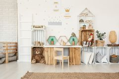 White kid room interior with gold posters on the wall, toys and. Pillows placed on crate shelves and desk with artificial cactuses stock photo