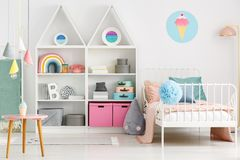 White kid`s room interior with a single bed, rainbow on the shel. F, pompom and ice-cream poster on the wall stock photo