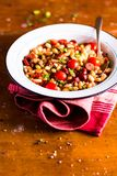 White kidney bean stew with pork sausages, cherry tomatoes, red bell pepper, fresh parsley in a plate on a wooden table, selective. Focus. Traditional balkan royalty free stock photography