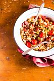White kidney bean stew with pork sausages, cherry tomatoes, red bell pepper, fresh parsley in a plate on a wooden table, selective. Focus. Traditional balkan stock photography