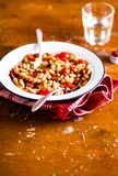 White kidney bean stew with pork sausages, cherry tomatoes, red bell pepper, fresh parsley in a plate on a wooden table, selective. Focus. Traditional balkan royalty free stock photos