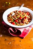 White kidney bean stew with pork sausages, cherry tomatoes, red bell pepper, fresh parsley in a plate on a wooden table, selective. Focus. Traditional balkan stock images