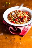 White kidney bean stew with pork sausages, cherry tomatoes, red bell pepper, fresh parsley in a plate on a wooden table, selective. Focus. Traditional balkan royalty free stock images