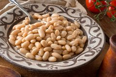 White Kidney Beans. A bowl of white kidney beans on a rustic wooden table top Stock Image