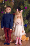 White Kids Posing in Front a Huge Christmas Tree Royalty Free Stock Images