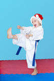 In a white kimono and wearing hat Santa Claus girl  blow kicks Royalty Free Stock Photos