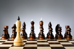 The white king on a background of black chess pieces Royalty Free Stock Images