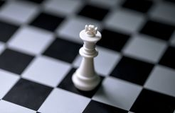 White king on chess board. Chess game figure on checkered board. White king alone on chessboard. Mate situation in chess rules. Business advantage or strong Royalty Free Stock Photography