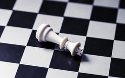 White king on chess board. King lost on checkered board. White king lies on chessboard. Mate situation in chess rules. Business advantage or strong leadership Stock Photo