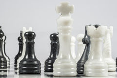 The white king falls under the checkmate of a black pawn. Marble pieces Stock Images