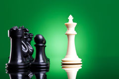 White king in front of the black chess pieces Royalty Free Stock Images