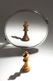A white king  is looking in a mirror to see himself as a black king. A  white king chess piece stands in front of a mirror. The reflection in the mirror shows a Royalty Free Stock Photography