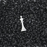 White king on a sea of pawns. 3D render of white chess king lying on hundreds of black pawns Royalty Free Stock Photos