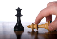 White king surrenders to black queen. Chess pieces with hand on a chessboard as a business concept Royalty Free Stock Images