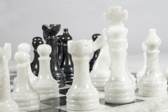 White king threatened in a chess game. Queen's Gambit. Marble pieces and chessboard Stock Images