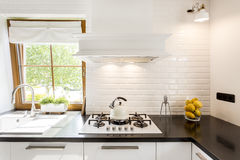 White kitchen with black countertop. Cropped shot of a bright kitchen room designed in white with a black countertop stock photo