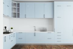 White kitchen, blue countertops. White kitchen interior with a dark wooden floor and blue countertops. Concept of a comfortable house. 3d rendering mock up Royalty Free Stock Images