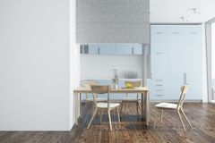 White kitchen, blue and white furniture side. White kitchen interior with a dark wooden floor and blue countertops. A wooden table with wooden chairs. A blank Royalty Free Stock Image