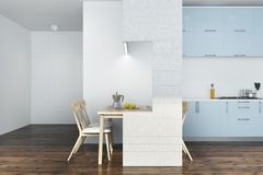 White kitchen, blue and white furniture. White kitchen interior with a dark wooden floor and blue countertops. A white table with wooden chairs. 3d rendering Royalty Free Stock Images