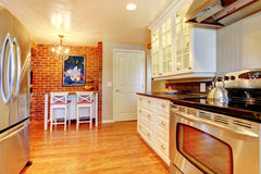 White kitchen with brick wall, hardwood and stainless steal stove. Royalty Free Stock Photography