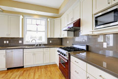 White kitchen with burgundy stove and grey counter tops Royalty Free Stock Images