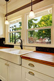 White kitchen cabinet with wooden counter top Royalty Free Stock Image