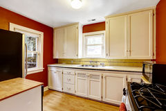 White kitchen cabinets with bright red wall Royalty Free Stock Image
