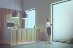 White kitchen corner, wooden countertops woman. White wall loft kitchen corner with a concrete floor, and wooden countertops under original lamps. A woman. 3d Stock Photos