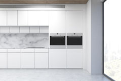 White kitchen counter. With two ovens and marble walls. There is a panoramic window with a city view. 3d rendering Royalty Free Stock Image