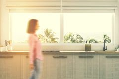 White kitchen countertops close up, woman. Wooden kitchen countertops with a built in sink standing under a large window with a tropical scenery. A woman 3d Royalty Free Stock Photo