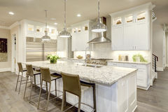 White kitchen design in new luxurious home. White kitchen design features large bar style kitchen island with granite countertop illuminated by modern pendant