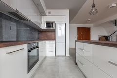 White kitchen with granite worktop royalty free stock photography