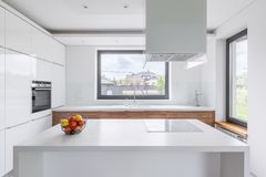 White kitchen with island. White kitchen with modern island, window and wooden cupboards royalty free stock photos