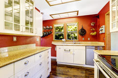 White kitchen room with contrast bright red walls Stock Photos